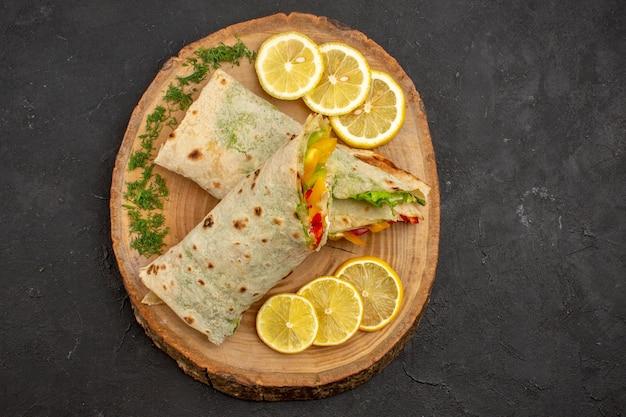 Bovenaanzicht van gesneden shaurma heerlijke vleessandwich met schijfjes citroen op zwart