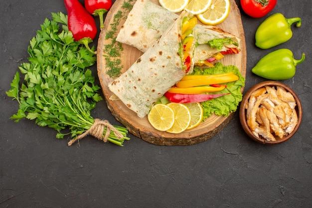 Bovenaanzicht van gesneden shaurma vleessandwich met schijfjes citroen en greens op zwart