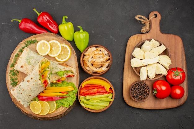 Bovenaanzicht van gesneden shaurma vleessandwich met schijfjes citroen en groenten op zwart