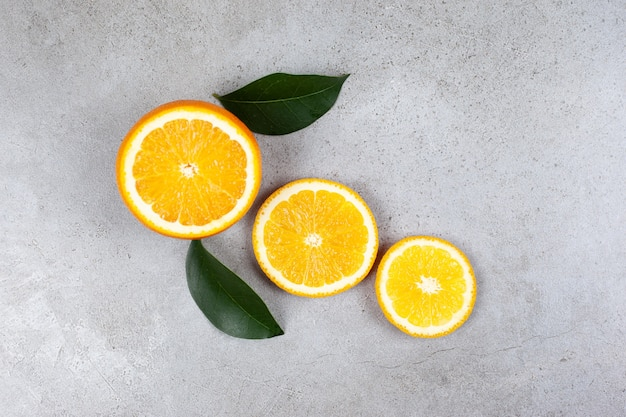 Bovenaanzicht van gesneden sinaasappel met bladeren op grijze tafel.