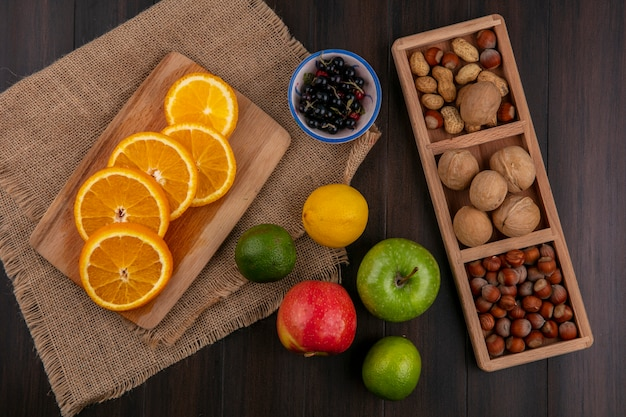 Bovenaanzicht van gesneden sinaasappel op een bord op een beige servet met appels citroen zwarte bessen en noten op een houten oppervlak