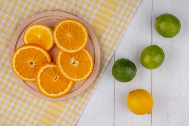 Bovenaanzicht van gesneden sinaasappel op een standaard op een gele geruite handdoek met limoenen (lemmetjes) op een wit oppervlak