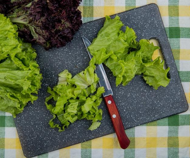 Bovenaanzicht van gesneden sla met mes op snijplank en hele met basilicum op geruite doek oppervlak