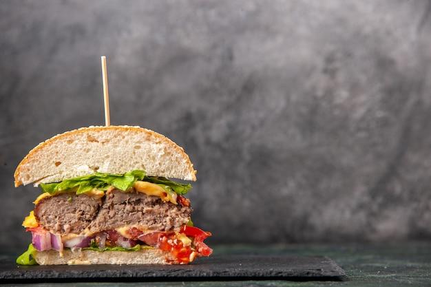 Bovenaanzicht van gesneden smakelijke sandwiches op zwarte lade aan de linkerkant op donkere mix kleur oppervlak
