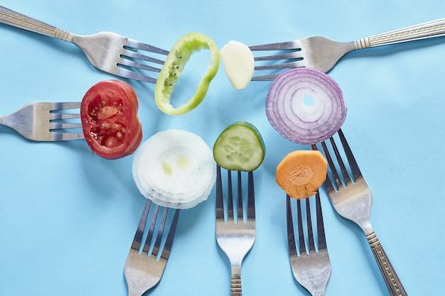 Bovenaanzicht van gesneden stukjes verse groenten en kruiden op vorken tegen een blauwe ondergrond