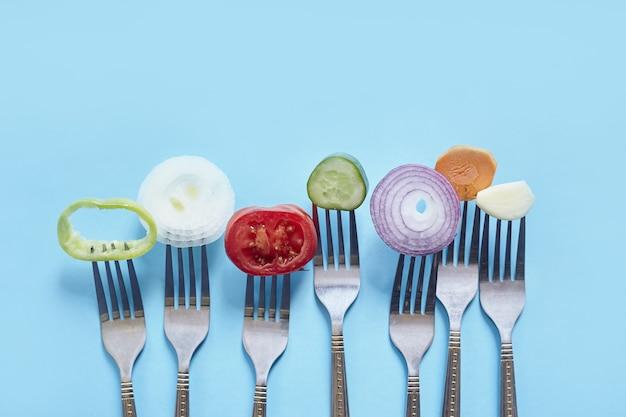 Bovenaanzicht van gesneden stukjes verse groenten en kruiden op vorken