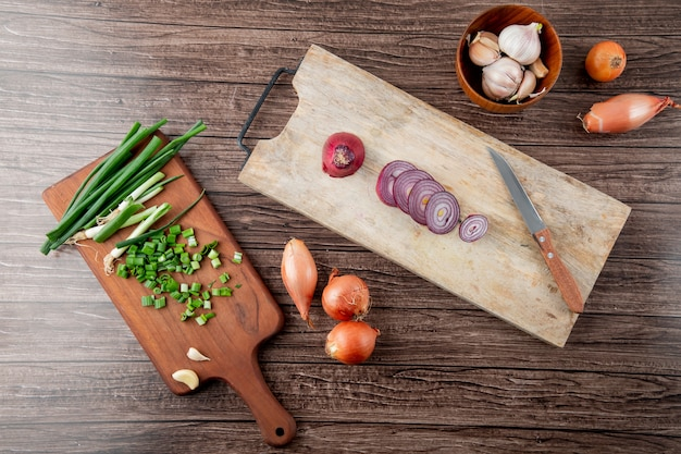 Bovenaanzicht van gesneden uien op snijplanken met knoflook en mes op houten achtergrond