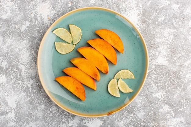 Bovenaanzicht van gesneden verse perziken binnen plaat met gesneden citroenen op het licht witte oppervlak