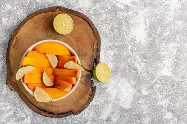 Bovenaanzicht van gesneden verse perziken in plaat met citroenen op het licht witte oppervlak