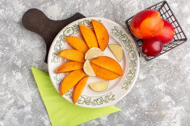 Bovenaanzicht van gesneden verse perziken in plaat met citroenen op wit oppervlak
