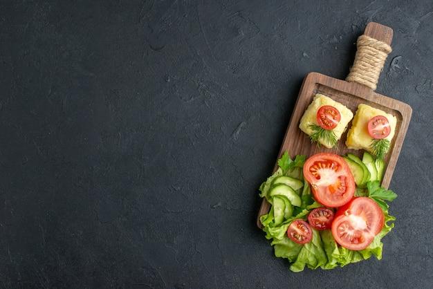Bovenaanzicht van gesneden verse tomaten en komkommers op houten bord aan de linkerkant op zwarte ondergrond