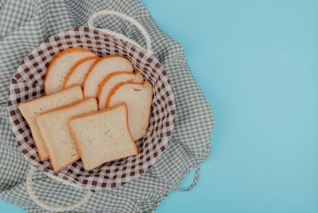 Bovenaanzicht van gesneden wit brood in mand op plaid doek en blauwe achtergrond met kopie ruimte