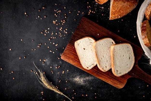 Bovenaanzicht van gesneden wit brood op snijplank met tarwe en zonnebloempitten op zwarte ondergrond