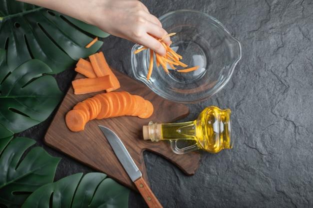Bovenaanzicht van gesneden wortelen op houten snijplank en vrouwelijke hand zet wortelschijfjes in kom.