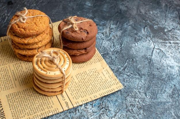 Bovenaanzicht van gestapelde heerlijke koekjes op een oude krant op donkere achtergrond