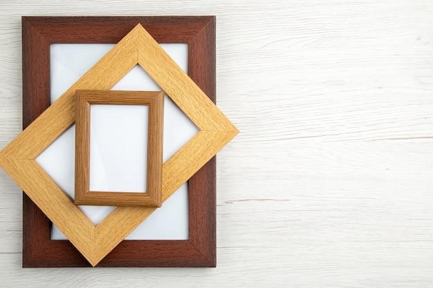 Bovenaanzicht van gestapelde kleine en grote lege afbeeldingsframes aan de rechterkant op witte houten