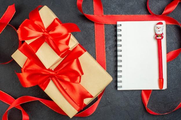 Bovenaanzicht van gestapelde mooie geschenken met rood lint en notitieboekje met pen op donkere achtergrond