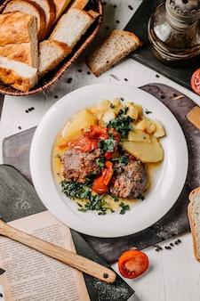 Bovenaanzicht van gestoofde vleesgroenten aardappelen en kruiden op een witte plaat
