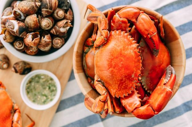 Bovenaanzicht van gestoomde gigantische modderkrabben in houten kom geserveerd met thaise pittige zeevruchten saus.