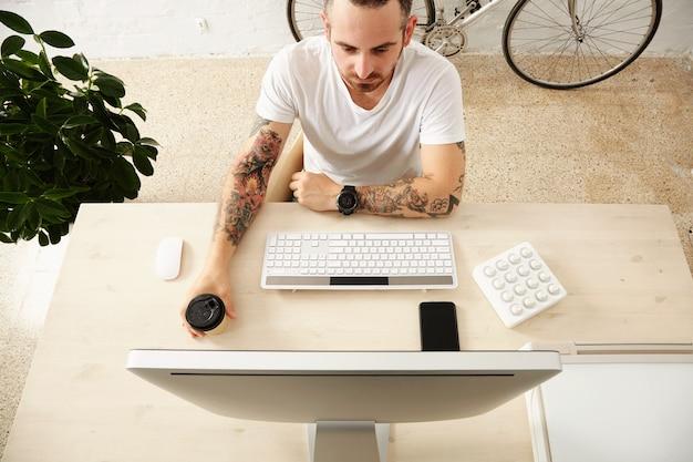 Bovenaanzicht van getatoeëerde freelancer houdt koffie uit papieren beker weg te halen terwijl hij op zijn computerscherm met midi music controller thuis desktop met slimme telefoon erop kijkt.