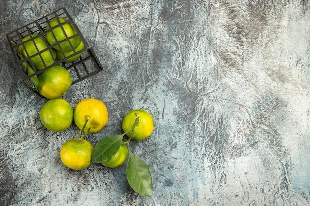 Bovenaanzicht van gevallen mand met verse groene mandarijnen in tweeën gesneden en gepelde mandarijn op grijze achtergrond