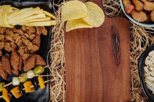 Bovenaanzicht van gevarieerde bier snacks chips chips ingelegde olijven brood crackers en kaas en een houten snijplank op stro