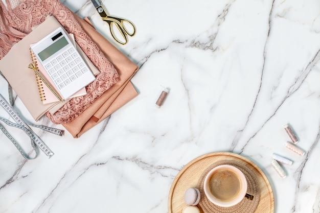 Bovenaanzicht van gevouwen koraalkleurig kant en zijden stoffen met draadspoelen, rekenmachine, blocnote, pen, meetlint, schaar op maat in de buurt van kopje koffie met macaronskoekjes op gouden dienblad. kopieer ruimte