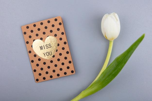Bovenaanzicht van geweldige witte tulp met liefde kaart op een grijze achtergrond