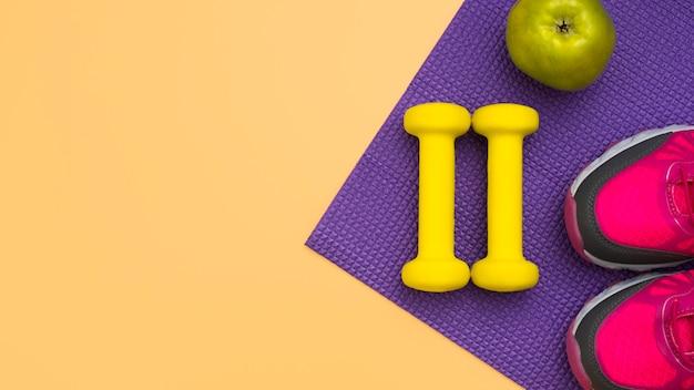 Bovenaanzicht van gewichten met appel en sneakers
