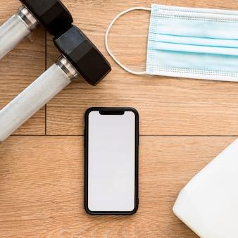Bovenaanzicht van gewichten met smartphone en medisch masker
