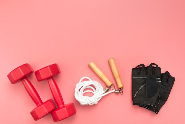 Bovenaanzicht van gewichten met springtouw en gym handschoenen