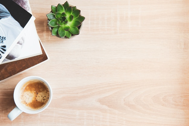 Bovenaanzicht van gezellige thuisscène. boeken, wollen deken, kopje koffie en vetplanten over hout. kopieer ruimte.