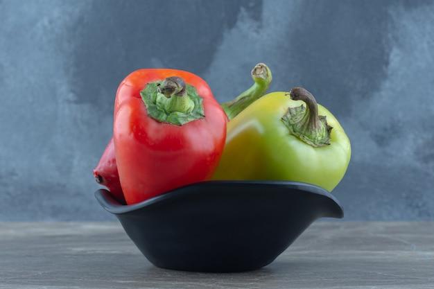 Bovenaanzicht van gezond voedsel in kom. verse biologische paprika's.