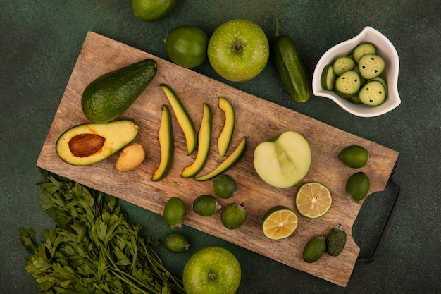 Bovenaanzicht van gezonde avocado met plakjes op een houten keukenbord met feijoas halve limoenen met gehakte plakjes komkommer op een kom met limoenen groene appels en peterselie geïsoleerd op een groene achtergrond