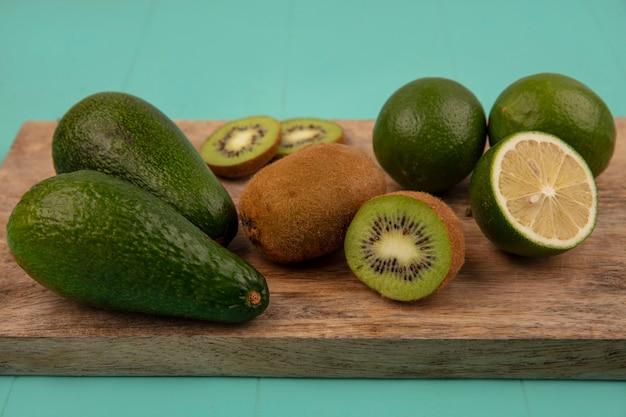 Bovenaanzicht van gezonde avocado's met limoenen en kiwi's op een houten keukenbord op een blauwe muur