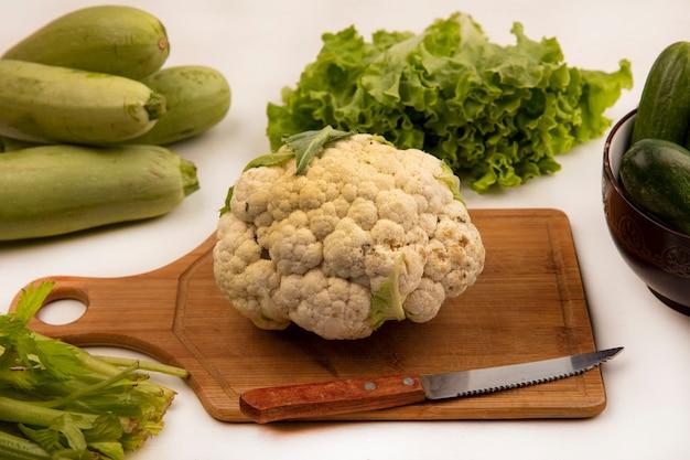 Bovenaanzicht van gezonde bloemkool op een houten keukenbord met mes met komkommers op een kom met sla, selderij en courgette geïsoleerd op een witte muur