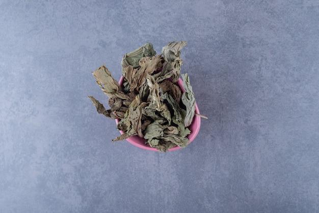 Bovenaanzicht van gezonde droge bladeren in roze kom.