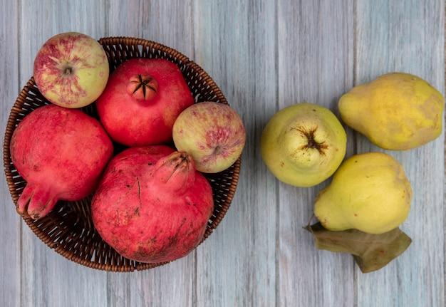 Bovenaanzicht van gezonde en verse granaatappels op een emmer met appels en kweeperen op een grijze achtergrond