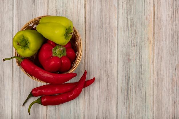 Bovenaanzicht van gezonde en verse paprika's op een emmer met chilipepers geïsoleerd op een grijze houten achtergrond met kopie ruimte