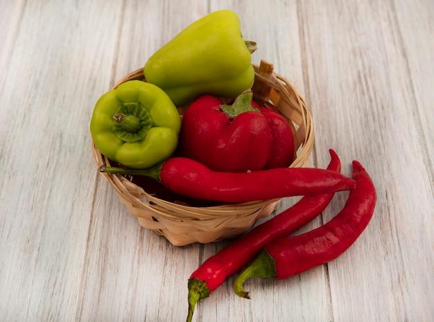 Bovenaanzicht van gezonde en verse paprika's op een emmer met chilipepers geïsoleerd op een grijze houten achtergrond