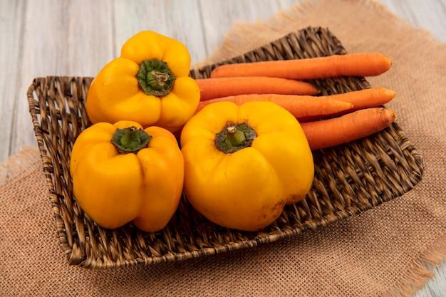 Bovenaanzicht van gezonde gele paprika met wortelen op een rieten dienblad op een zakdoek op een grijze houten ondergrond