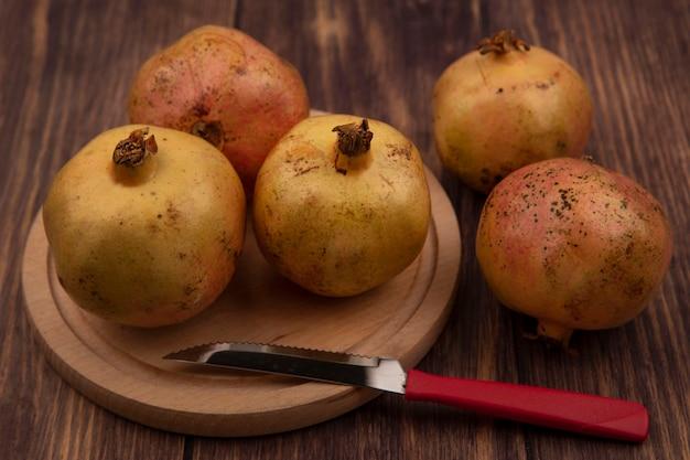 Bovenaanzicht van gezonde granaatappels op een houten keukenbord met mes op een houten oppervlak