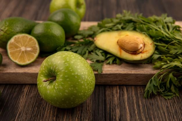 Bovenaanzicht van gezonde groene appel met limoenen, avocado's en peterselie geïsoleerd op een houten keukenbord op een houten muur