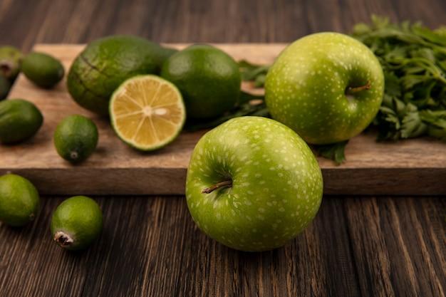 Bovenaanzicht van gezonde groene appels op een houten keukenbord met feijoas limoenen, avocado's en peterselie geïsoleerd op een houten muur