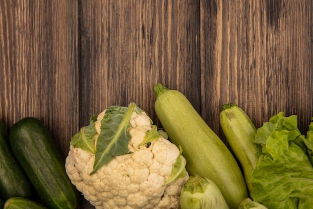 Bovenaanzicht van gezonde groenten zoals courgettes, komkommers, sla, bloemkool en selderij geïsoleerd op een houten muur met kopie ruimte