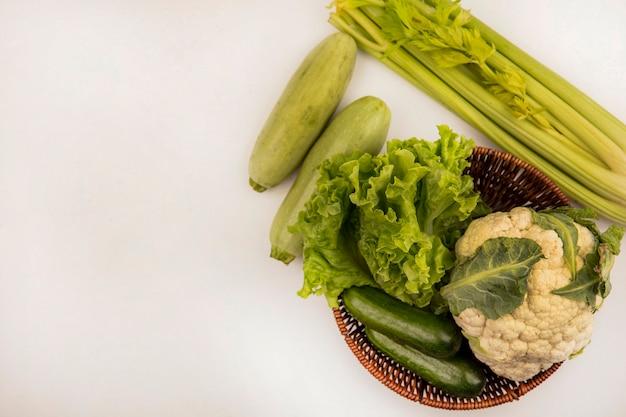 Bovenaanzicht van gezonde groenten zoals sla, bloemkool en komkommers op een emmer met selderij en courgettes geïsoleerd op een witte muur met kopie ruimte