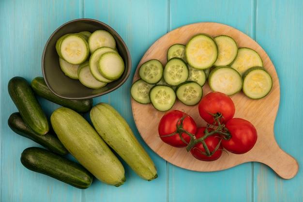 Bovenaanzicht van gezonde groenten zoals tomaten, gehakte komkommers en courgettes op een houten keukenbord met komkommers en courgettes geïsoleerd op een blauwe houten ondergrond