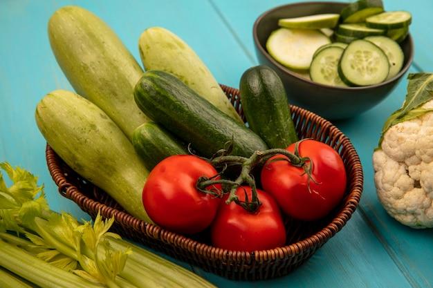 Bovenaanzicht van gezonde groenten zoals tomaten, komkommers en courgettes op een emmer met bloemkool en selderij geïsoleerd op een blauwe houten muur
