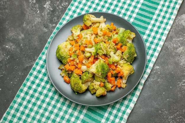 Bovenaanzicht van gezonde groentesalade op groene gestripte handdoek op grijze tafel