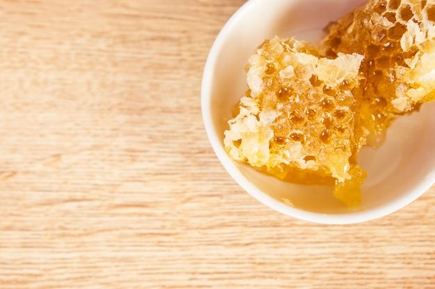 Bovenaanzicht van gezonde honingraat in kom op houten tafel